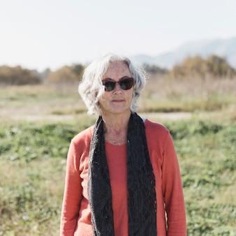 Colpo medio donna con occhiali da sole e sciarpa