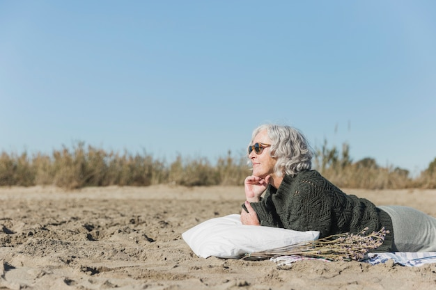 Colpo medio donna con occhiali da sole sulla spiaggia
