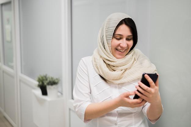 Colpo medio donna con smartphone