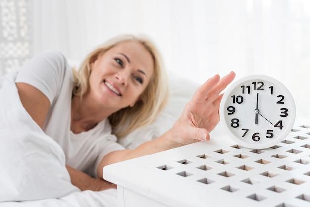 Colpo medio donna felice con orologio