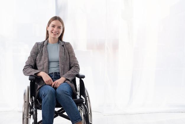 Colpo medio donna felice in sedia a rotelle