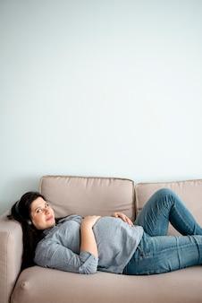 Colpo medio donna incinta posa sul divano