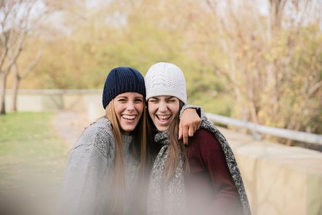 Colpo medio due giovani donne abbraccianti nel parco