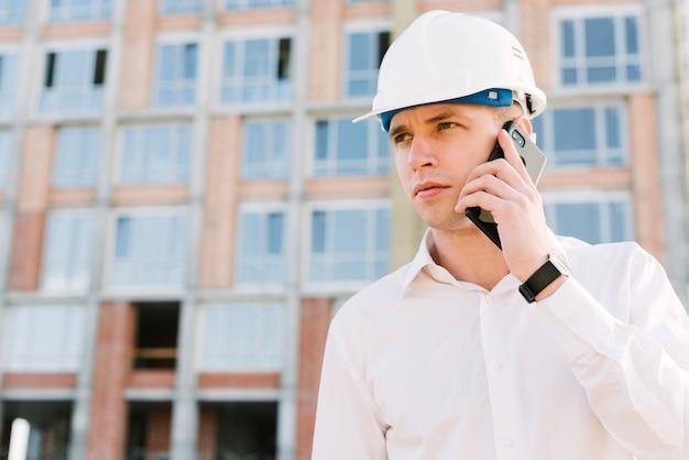 Colpo medio giovane con casco parlando al telefono