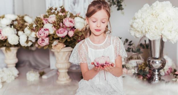 Colpo medio innocente del fiore della tenuta della ragazza