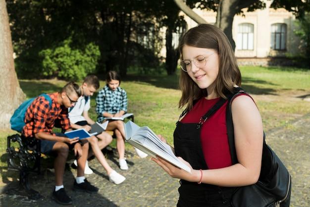 Colpo medio obliquamente della ragazza del highshool che legge un libro