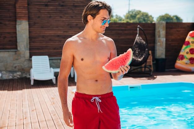 Colpo medio uomo bello in piscina