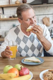 Colpo medio uomo mangia un panino
