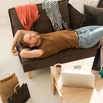 Colpo medio uomo posa sul divano