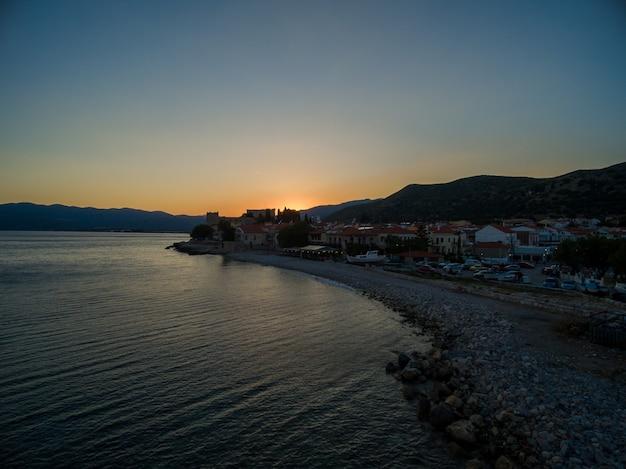 Colpo mozzafiato del sole che sorge sulla spiaggia di samos, in grecia