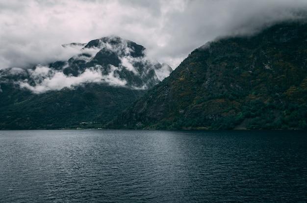 Colpo mozzafiato di un lago circondato dalle montagne innevate sotto il cielo nebbioso in norvegia