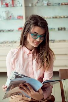 Colpo orizzontale del cliente femminile caucasico di bell'aspetto seduto in occhiali prescritti alla moda, leggendo la rivista e sorridente, in attesa in coda per l'oculista per un controllo visivo regolare