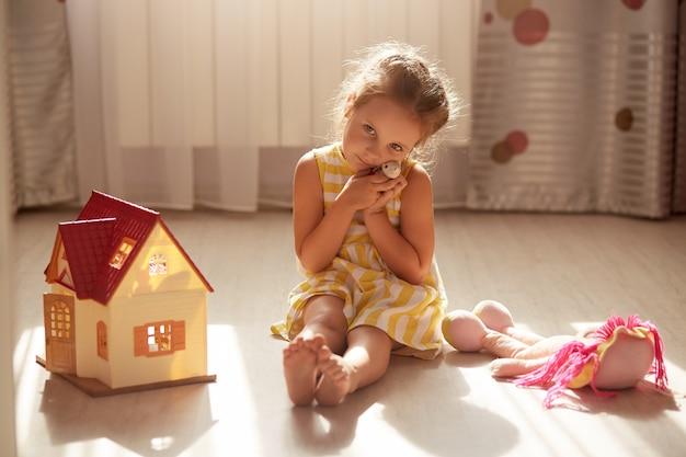 Colpo orizzontale della bambina che abbraccia il suo peluche preferito, giocando a casa. bambino caucasico che porta vestito giallo, con espressione facciale triste. infanzia, comfort domestico, concetto di amicizia.