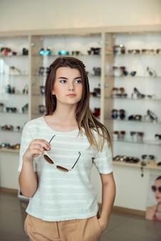 Colpo orizzontale della donna sveglia con taglio di capelli alla moda che sta nel deposito ottico mentre selezionando gli occhiali da sole