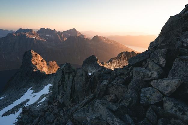 Colpo orizzontale delle montagne rocciose coperte di neve durante l'alba