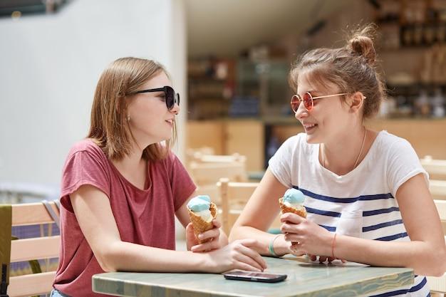 Colpo orizzontale di amichevoli si incontrano nel caffè, mangiano il gelato e hanno espressioni positive, godono il riposo estivo, indossano magliette casual, posano contro l'interno della caffetteria. concetto di amicizia