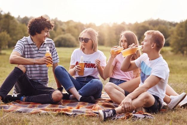 Colpo orizzontale di amici felici fare picnic, bere birra fresca, godersi il clima estivo, sedersi sul plaid, condividere le ultime notizie, posare contro la natura verde