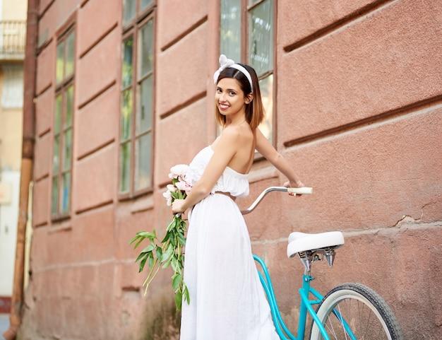 Colpo orizzontale di angolo basso della donna felice che cammina con la sua bicicletta sulla via della città che sorride alla macchina fotografica sopra la sua spalla