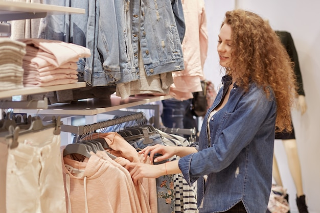 Colpo orizzontale di giovane femmina alla moda shopaholic sceglie i vestiti sui ganci, soddisfatto di passare il tempo libero a fare shopping, cerca di trovare qualcosa di adatto.