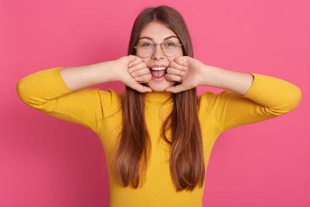 Colpo orizzontale di magnetica adorabile ragazza giovane apertura bocca ampiamente, guardando direttamente mettendo vicino al viso