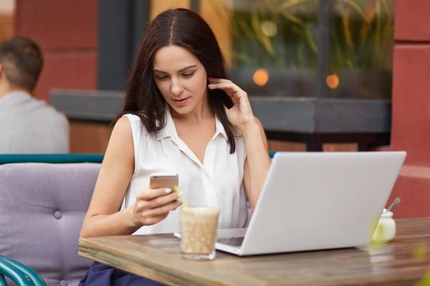 Colpo orizzontale di occupato libero professionista femminile tiene il telefono cellulare, messaggi di testo online, utilizza un computer portatile, beve frullato, pone nel ristorante all'aperto, vestito in abiti bianchi
