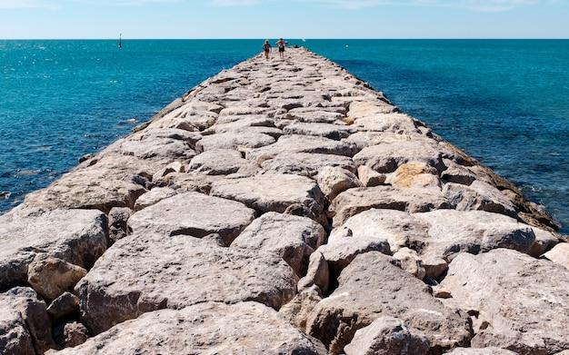 Colpo orizzontale di una via di pietra su un corpo idrico con persone che camminano su di esso.