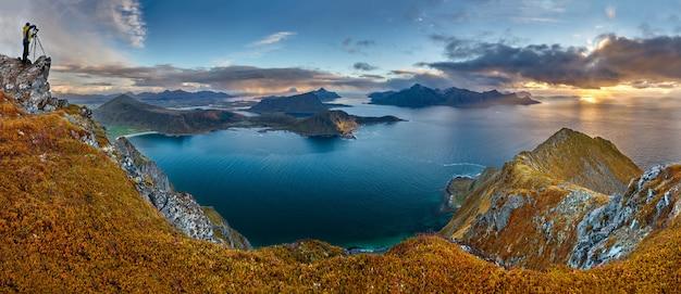 Colpo panoramico della collina veggen vicino al mare sotto un cielo blu in norvegia