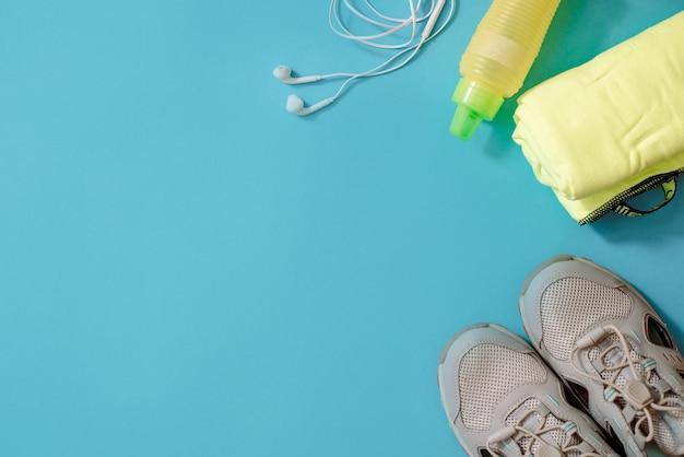 Colpo piatto dell'attrezzatura sportiva. scarpe da ginnastica, manubri, auricolari e telefono sul blu