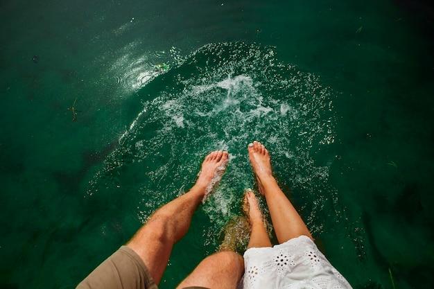 Colpo piatto laici delle coppie che giocano in acqua con i piedi