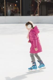 Colpo pieno adorabile di pattinaggio su ghiaccio della ragazza