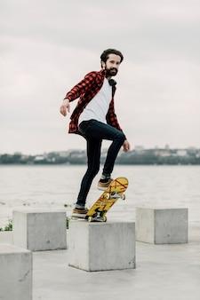 Colpo pieno dell'uomo che equilibra sullo skateboard