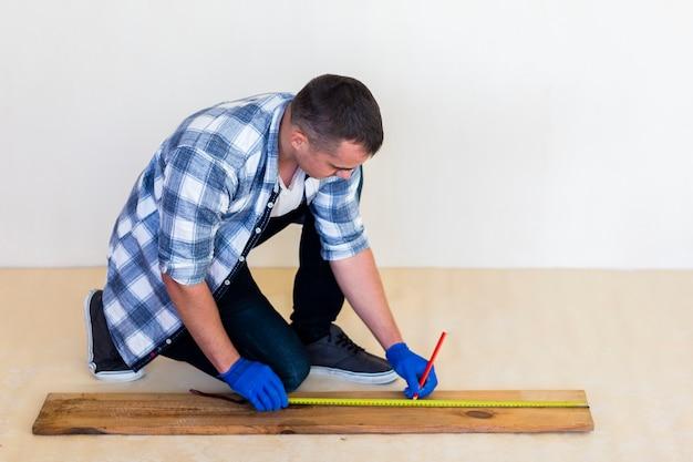 Colpo pieno dell'uomo che prende misura su legno