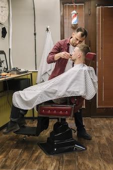 Colpo pieno dell'uomo che rade la sua barba