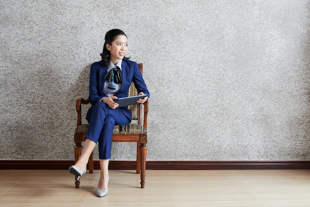 Colpo pieno della donna di classe di affari con la compressa che guarda a partire dalla macchina fotografica che si siede nella sedia