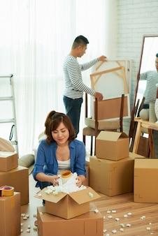 Colpo pieno delle coppie che disimballano gli effetti personali in un nuovo appartamento