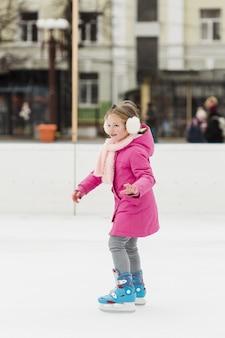 Colpo pieno di bello pattinaggio su ghiaccio della ragazza