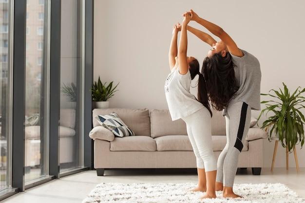 Colpo pieno donna e ragazza che fanno yoga