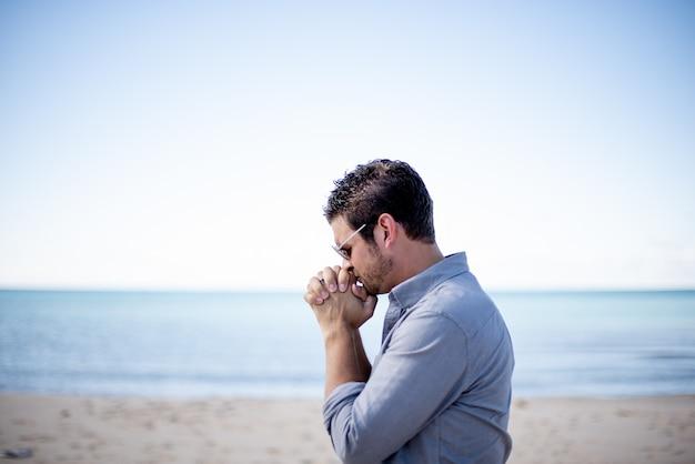 Colpo poco profondo del fuoco di un maschio vicino alla spiaggia con le sue mani vicino alla sua bocca mentre pregava