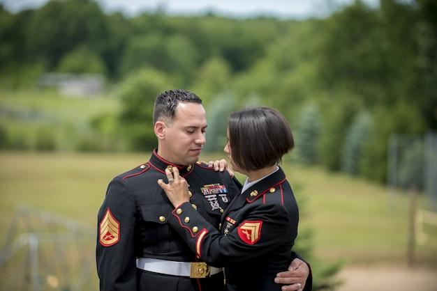 Colpo poco profondo del fuoco di una coppia militare che abbraccia