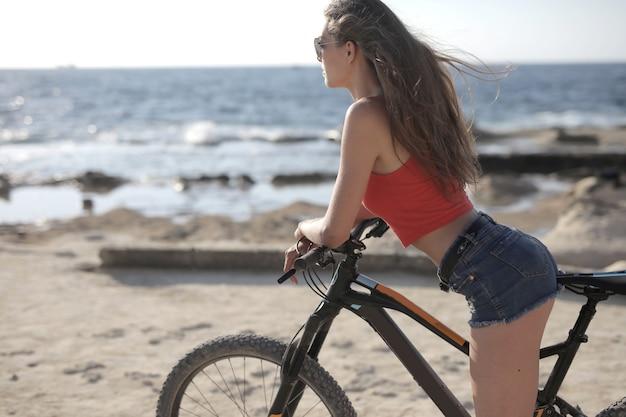 Colpo poco profondo del fuoco di una donna che guida una bicicletta nella spiaggia