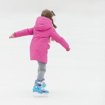 Colpo posteriore adorabile di pattinaggio su ghiaccio della ragazza