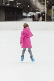 Colpo posteriore di pattinaggio su ghiaccio della ragazza