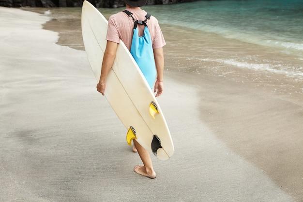Colpo potato dalla parte posteriore dell'uomo alla moda che porta la sua tavola da surf bianca dopo l'esercizio del surf. surfista caucasico che tiene bodyboard sotto il suo braccio