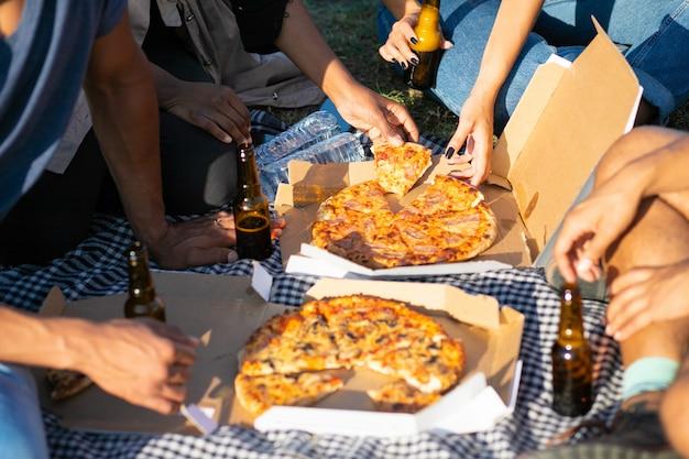 Colpo potato degli amici che hanno picnic nel parco di estate. giovani seduti sul prato con pizza e birra. concetto di pic-nic