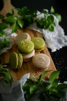 Colpo potato dei macarons dolci francesi sul vassoio di legno