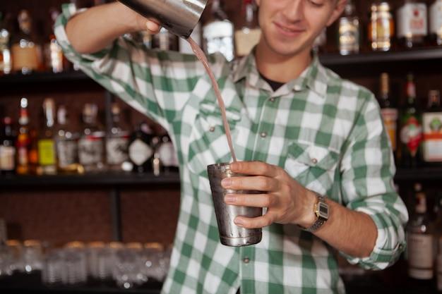 Colpo potato del barista professionista allegro che prepara cocktail per un cliente, usando la latta d'acciaio dell'agitatore