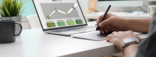 Colpo potato del grafico che lavora al progetto infographic con la compressa e il computer portatile del disegno