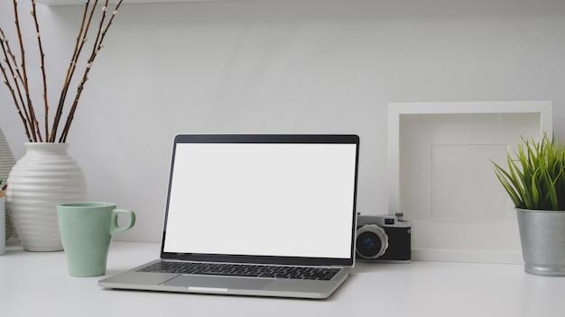 Colpo potato del posto di lavoro con il computer portatile, la struttura, le decorazioni e la macchina fotografica dello schermo in bianco sullo scrittorio bianco