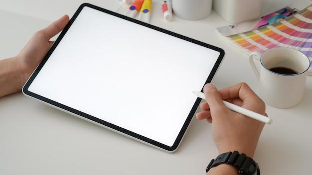 Colpo potato del progettista che lavora alla compressa digitale con la penna dello stilo e rifornimenti del progettista