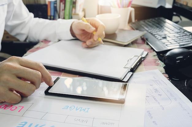 Colpo potato del progettista creativo del sito web facendo uso dello smartphone e schizzando il modello della disposizione di web alla scrivania.